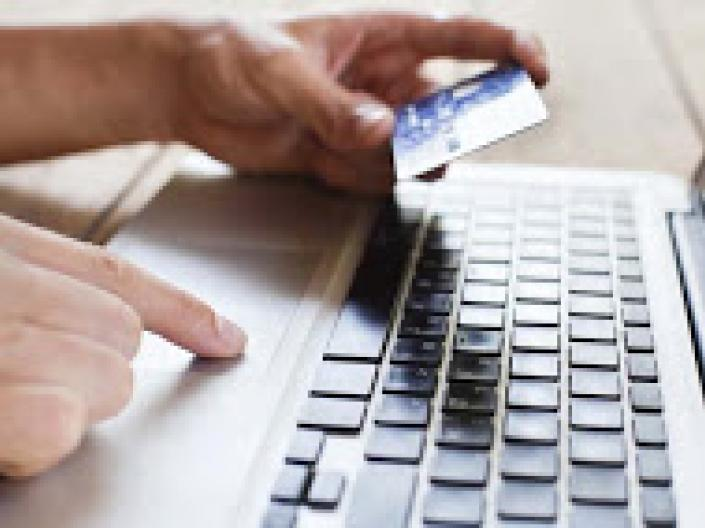 Person typing on a computer keyboard holding a credit card