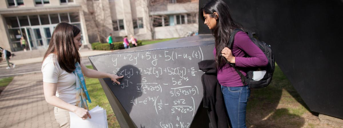 Two female students working on a math problem on a chalkboard in the center of the CWRU Quad.