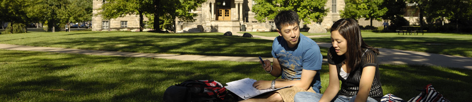 Students sit on a campus lawn and study.