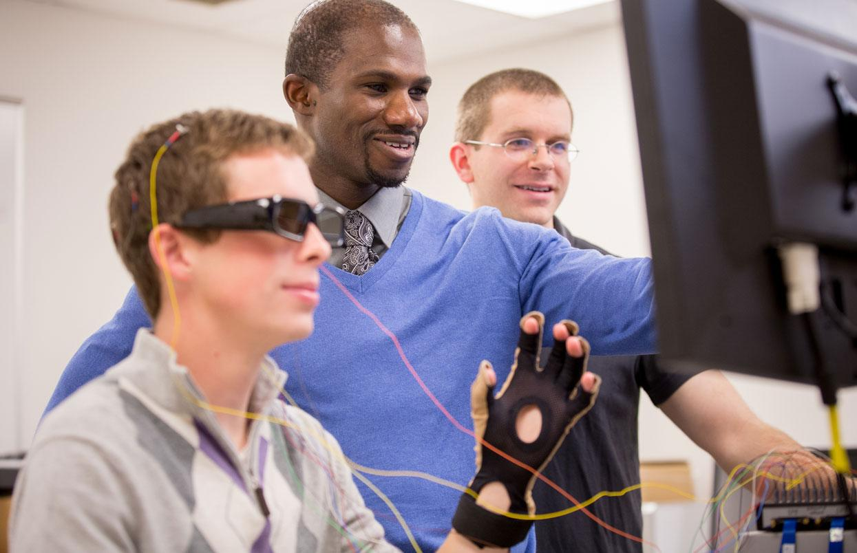 CWRU student wearing a headset and faculty members looking at a computer