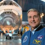 Former CWRU student, Astronaut Don Thomas in front of a shuttle in hangar.