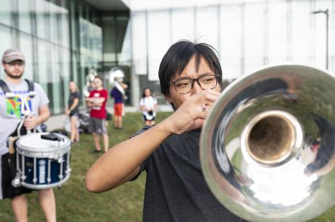 Student plays trumpet outside, drummer in the background