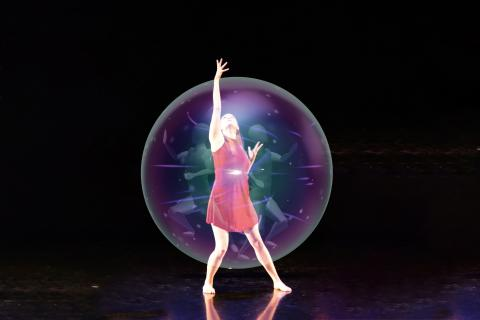 Student dancer reaches upward from holographic bubble