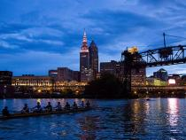 CWRU team rowing at night by downtown Cleveland