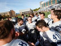 CWRU football team in a huddle at the beginning of a game