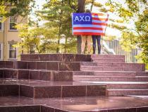 Sorority sister with flag posing on a fountain on campus