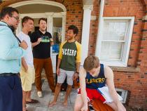 group of male students hanging out in front of a residence hall