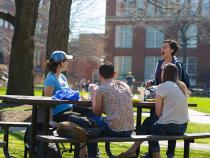 Students sitting at a picnic table outside of their dorms
