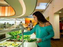 Student grabbing a salad for lunch from the salad bar