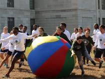 Students chasing a huge ball around outside the Tink
