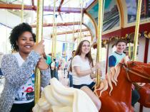 three students sitting on carousel horses at the Cleveland History Center