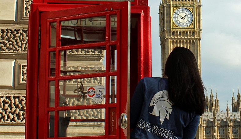 CWRU student leaning out of phone booth in London