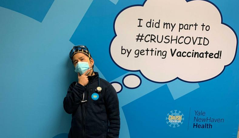 CWRU Jack Cheng poses in front of a sign signifying he received his COVID vaccine