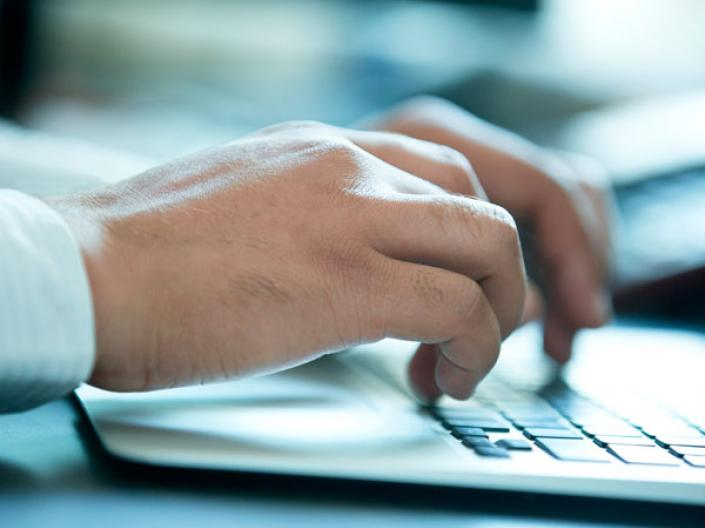Stock image of hands typing on a computer