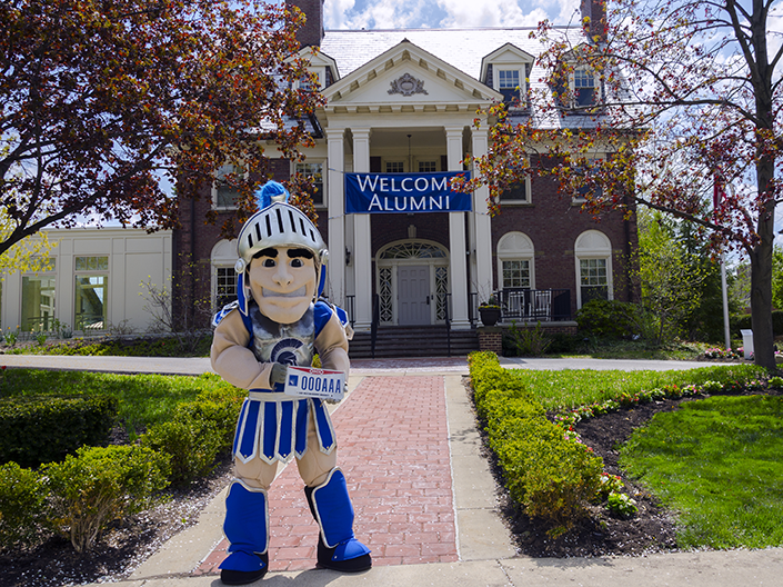 Image of Spartie, on a sunny day standing in front of the Linsalata Alumni Center holding the Ohio CWRU Alumni License Plate