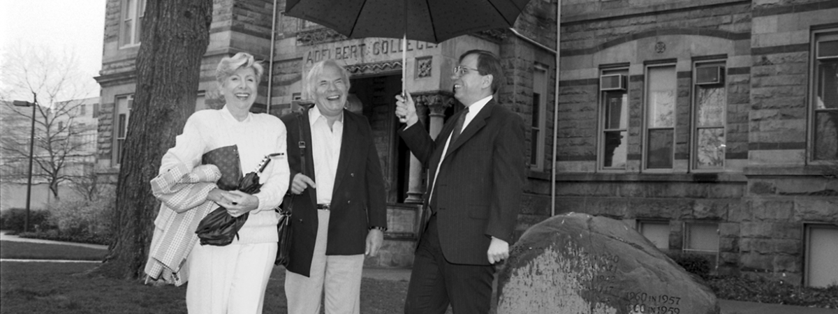 Photo of Richard Baznik holding an umbrella for Mr. and Mrs. Arthur Behrman in 1989 in front of Adelbert