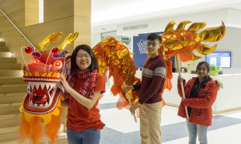 Three CWRU international students pose with the dragon from the 2018 Lunar New Year celebration