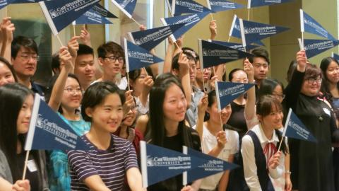 Group of incoming CWRU students, posed and smiling for the camera, waving CWRU pennant flags