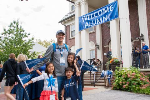 Photo of Arnold Huffman and his children, posed and smiling wearing CWRU gear outside of the Linsalata Alumni Center