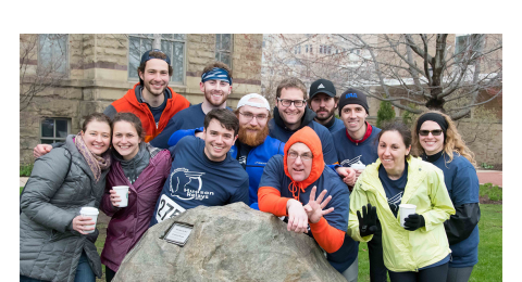 Photo of group of alumni on the 2018 Hudson Relays team, posed and smiling around the rock near Adelbert Hall