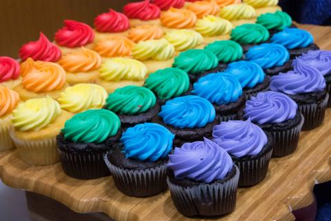 several rows of frosted cupcakes form a rainbow