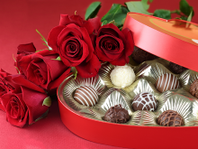Photo of red roses, laying on top of an open box of assorted chocolates
