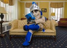 CWRU mascot Sparty the Spartan sitting on a couch in the Linsalata Alumni Center reading Think Magazine