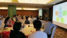 Photo of students at the Shanghai Summer Send-Off, gathered around tables looking at a presentation