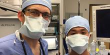 Photo of two people in scrubs wearing face masks in an operating room
