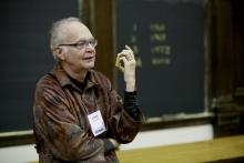 Don Knuth stands in front of the blackboard in a lecture hall