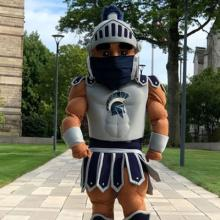 Case Western Reserve University mascot Spartie stands on the Binary Walkway wearing a facemask