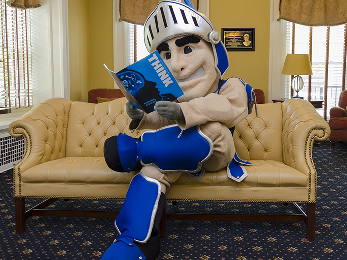Photo of Spartie, sitting on the couch in the Linsalata Alumni Center, reading Think magazine.