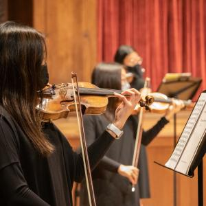 Orchestra students perform masked at the Maltz Performing Arts Center