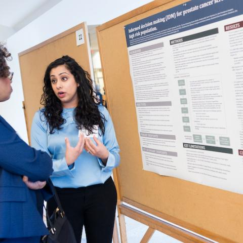 Image of an attendee presenting their research poster at the 2018 Cancer Disparities Symposium
