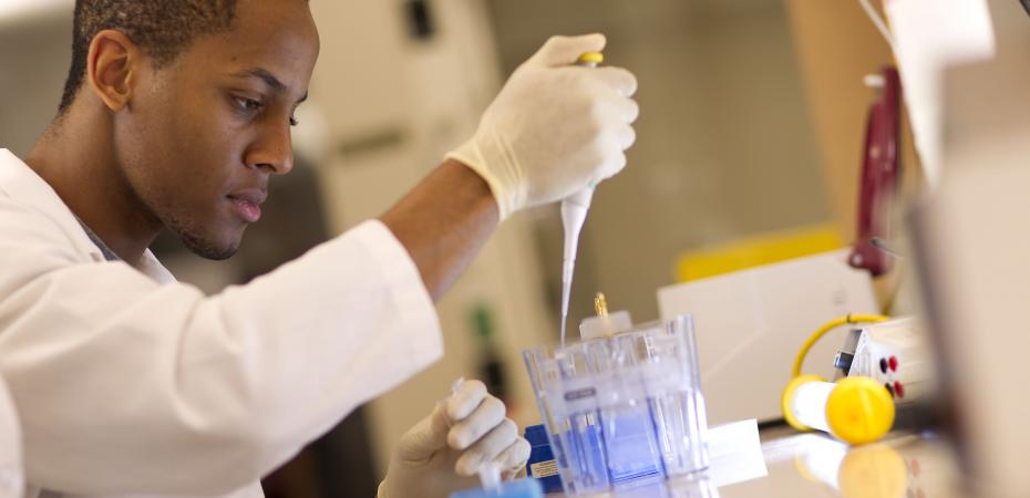Man in lab pipetting