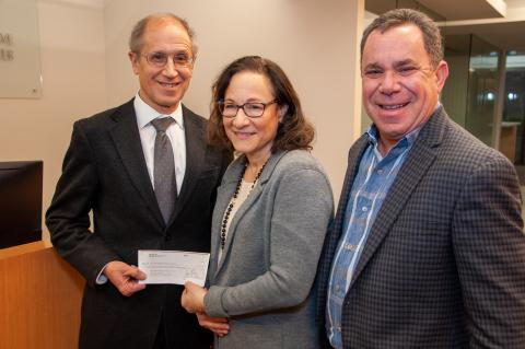 Dr. Gerson, Patti Berns, and Jonathon Berns stand smiling in the Case Comprehensive Cancer Center office. Dr. Gerson and Patti are holding a check.
