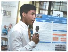 Connor Harris speaking into a microphone in front of a research poster