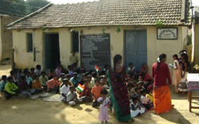 Young children sit outside their village school room in Bangalore