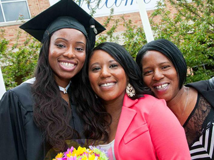 image of smiling graduating student with family members