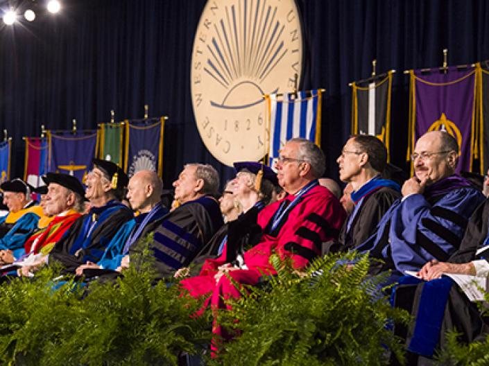 Faculty and other leaders sitting on stage at commencement.