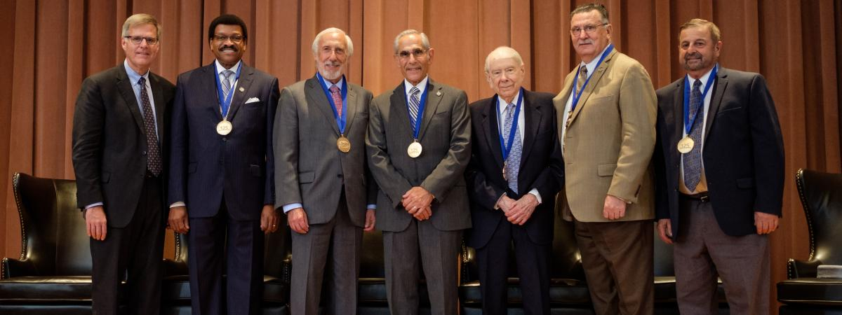 A group of dental alumni wearing medals for their achievements