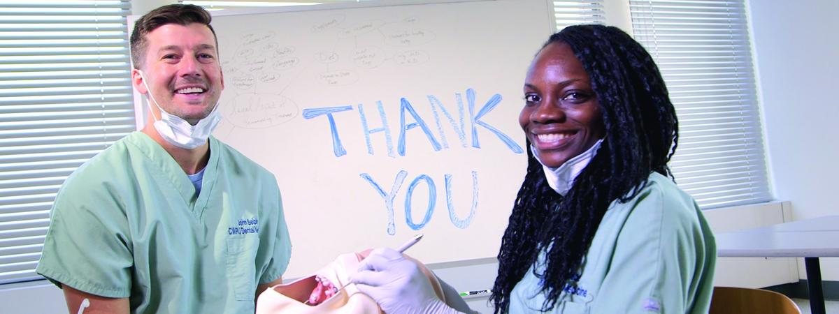 "Two dental students in front of white board reading ""Thank you"""