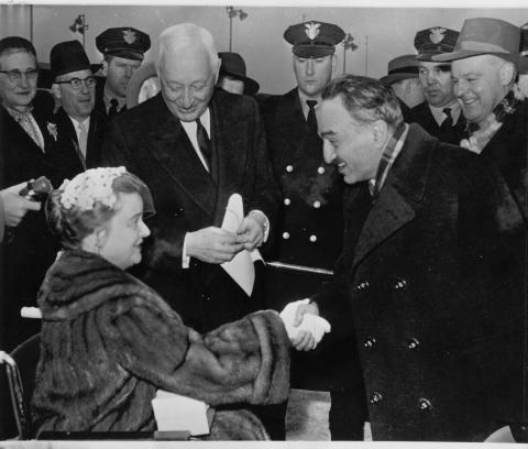 Anastas Mikoyan (right) meets Cyrus Eaton (standing) and his wife, Anne (seated in a wheelchair) upon his arrival in Cleveland, 7 January 1959.