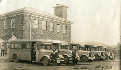 Five buses are lined up in a row in front of the North Olmsted Municipal Bus Line garage in this circa 1932 photograph with several drivers posed with the buses.