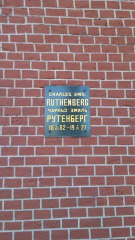 A small metal plaque with writing in English and Russian on a red brick wall marks the interment site of Charles Ruthenberg