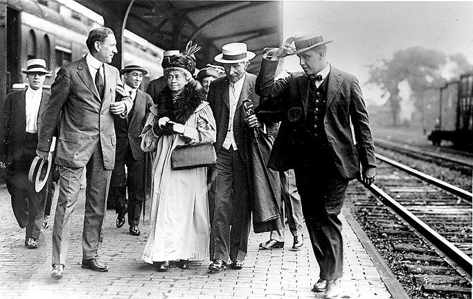 Standard Oil Co. founder John D. Rockefeller escorts sister-in-law Lucy Spelman through Coit Rd. Railroad Station in East Cleveland, en route to Rockefeller