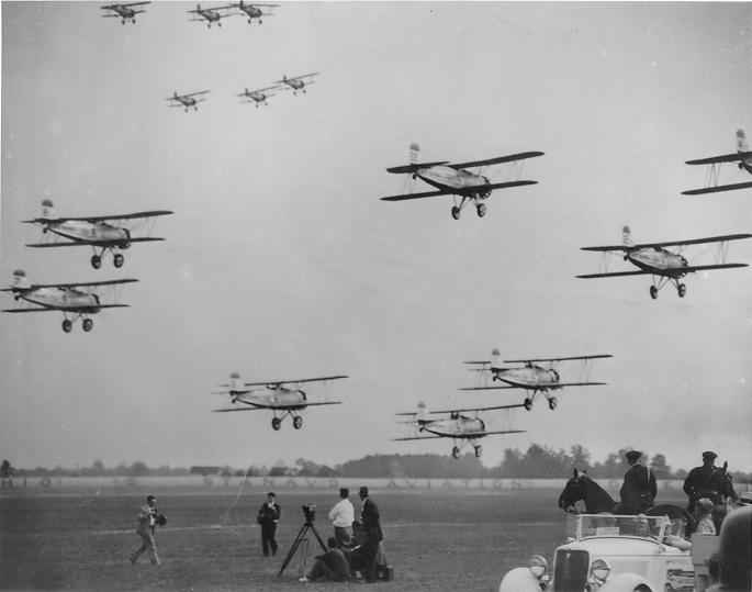 Multiple aircraft fly in formation at the National Air Races held in Cleveland, July 1935. WRHS.