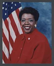 Stephanie Tubbs Jones in a red shirt, sitting in front of an American flag.