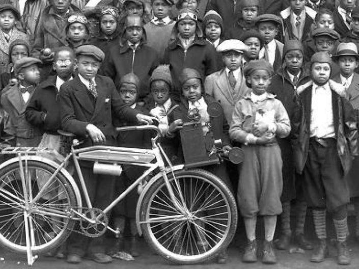 A group of newsboys with one kid holding a bike