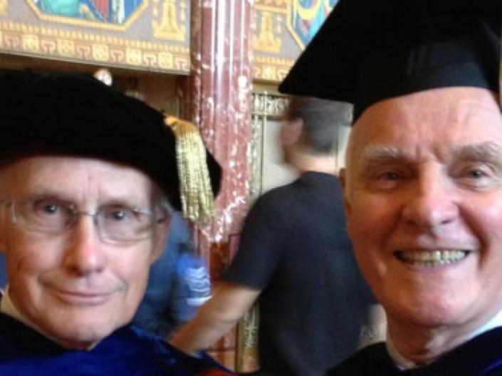 Two professors standing during graduation.